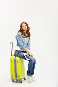 Jeune belle femme caucasienne est assise sur suitecase et attend son vol.