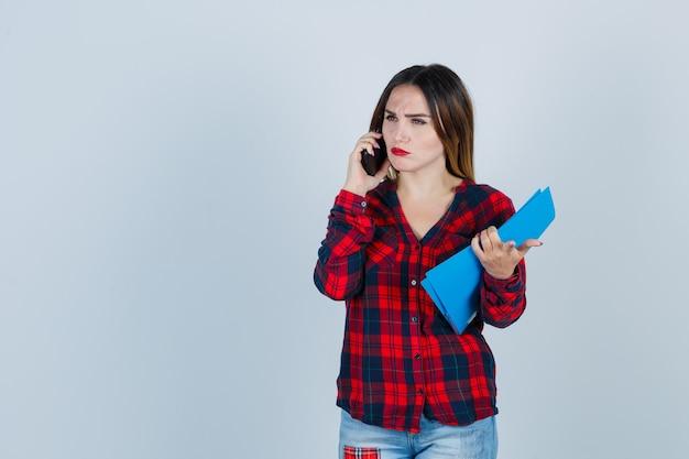 Jeune belle femme en chemise décontractée, jeans tenant un dossier tout en parlant au téléphone, pointant vers l'avant et l'air perplexe, vue de face.