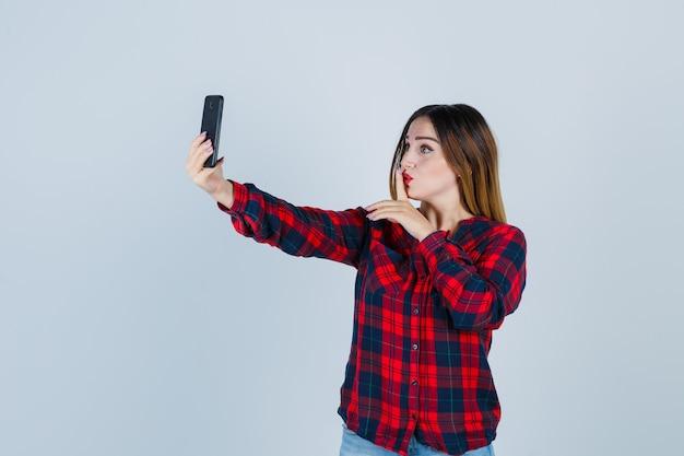 Jeune belle femme en chemise décontractée prenant un selfie, montrant un geste de silence et semblant concentrée, vue de face.