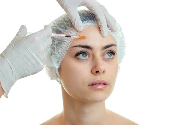 Jeune belle femme chez le chirurgien plasticien isolé sur mur blanc