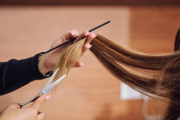 Jeune belle femme cliente fait une coupe de cheveux d'un coiffeur professionnel dans un salon de beauté