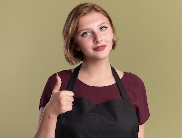 Jeune belle femme coiffeur en tablier regardant avant montrant les pouces vers le haut souriant debout sur le mur vert