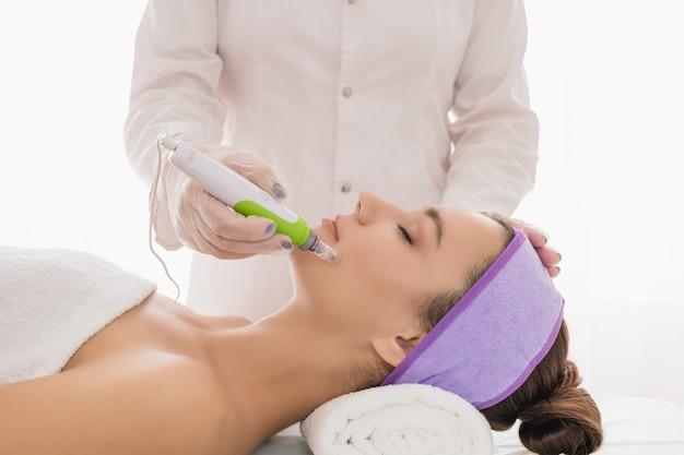 Jeune belle femme dans le bureau des cosmétologues recevant un traitement du visage