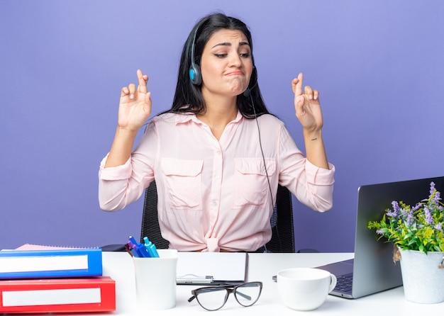 Jeune belle femme dans des vêtements décontractés portant un casque faisant des vœux croisant les doigts avec une expression d'espoir assise à la table avec un ordinateur portable sur un mur bleu travaillant au bureau
