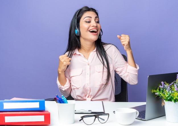 Jeune belle femme dans des vêtements décontractés portant un casque avec microphone heureux et excité, serrant les poings assis à la table avec un ordinateur portable sur un mur bleu travaillant au bureau