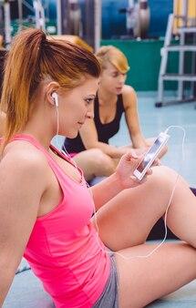 Jeune belle femme écoutant de la musique dans son smartphone pendant qu'un ami parle assis sur le sol du centre de remise en forme