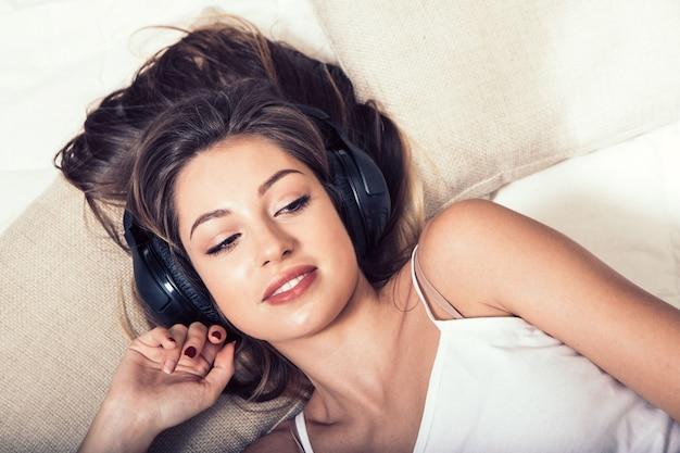 Jeune belle femme écouteurs écoutant de la musique sur le lit