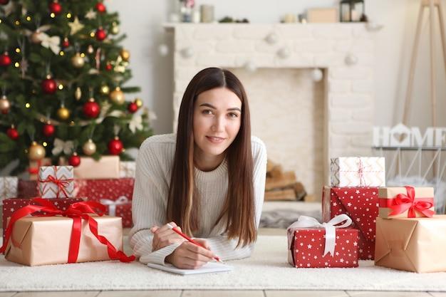 Jeune belle femme écrivant des achats ou une liste de souhaits pour noël à la maison