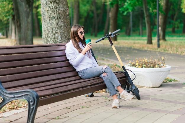 Jeune belle femme élégante équitation scooter électrique par parc d'automne, transport écologique