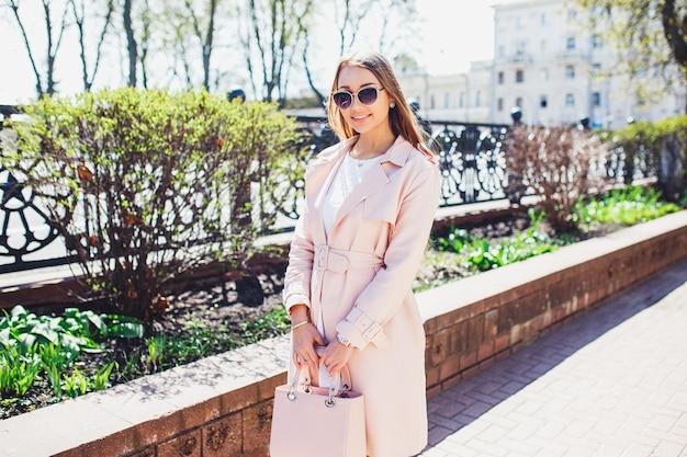 Jeune belle femme élégante qui marche et qui pose en robe blanche et manteau rose en ville. portrait d'été en plein air de jeune femme chic à lunettes de soleil
