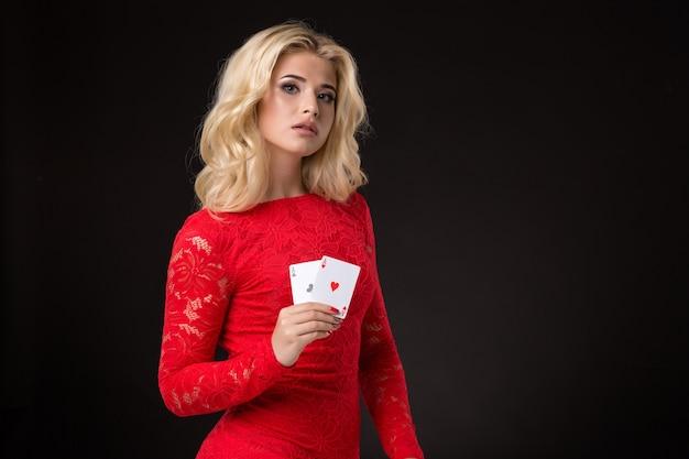 Jeune belle femme émotive avec des cartes dans des mains sur un fond noir dans le poker de studio