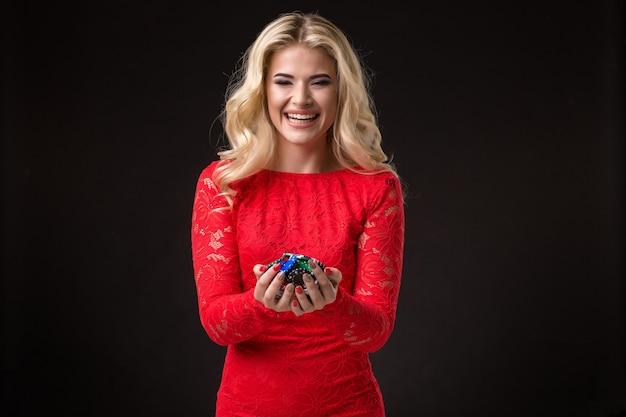 Jeune belle femme émotive avec des jetons dans les mains sur fond noir dans le studio de poker