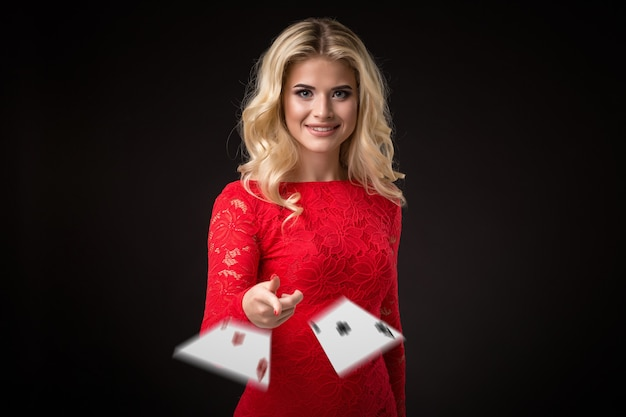 La jeune belle femme émotive jette des cartes sur un fond noir dans le poker de studio