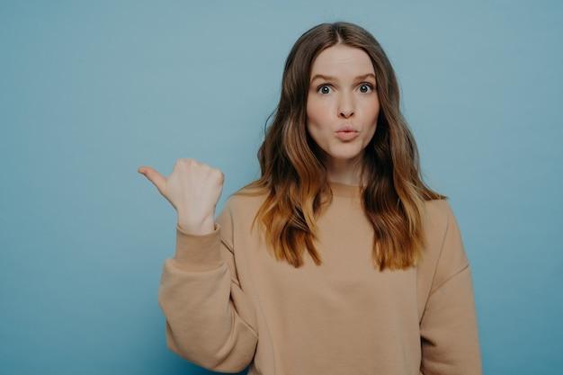 Jeune belle femme étonnée portant des vêtements décontractés pointant vers l'espace de copie avec une expression de visage wow et regardant la caméra tout en se tenant isolée sur fond bleu studio