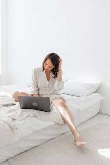 Une jeune et belle femme européenne allongée sur un lit dans une chambre blanche avec un ordinateur portable
