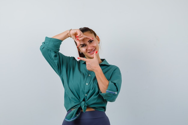 Jeune belle femme faisant un geste de cadre en chemise verte et à la recherche de bonheur. vue de face.