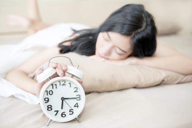 Jeune belle femme fatiguée et paresseuse essaie de se réveiller et d'éteindre le réveil