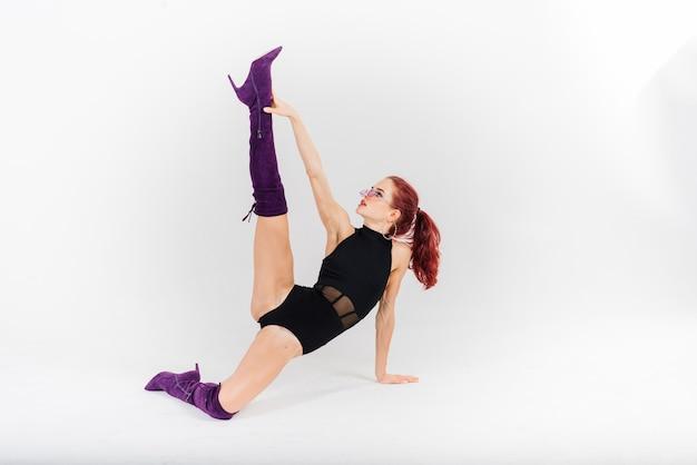 Jeune belle femme flexible dans une combinaison noire et talons hauts pose dans un studio de danse.