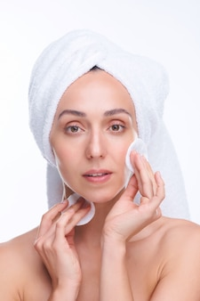 Jeune belle femme fraîche avec des cotons vous regardant tout en appliquant une lotion hydratante sur le visage de manière isolée