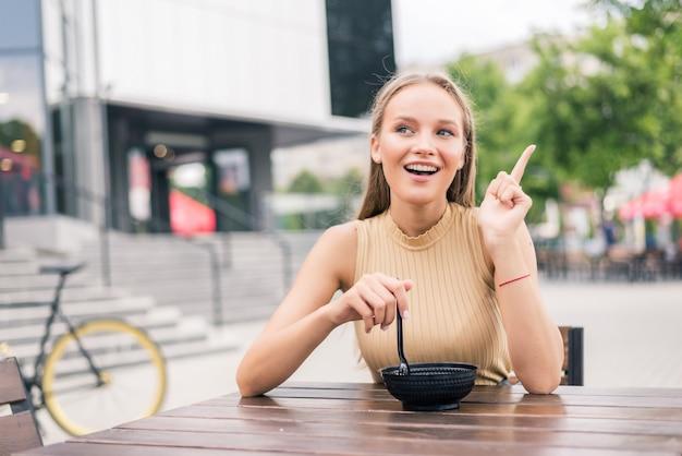 Jeune belle femme geste avec le doigt tout en mangeant de la salade au café en plein air