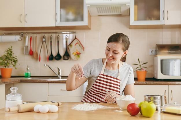 La jeune belle femme heureuse assise à une table avec de la farine et va préparer des gâteaux dans la cuisine. cuisiner à la maison. préparer la nourriture.
