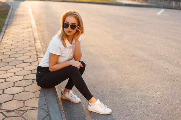 Jeune belle femme hipster élégante avec des lunettes de soleil dans un polo blanc et un jean noir avec des baskets assis dans la rue au coucher du soleil. fille à la mode en vêtements d'été
