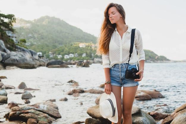 Jeune belle femme hipster en vacances d'été en asie, détente sur la plage tropicale, appareil photo numérique, style boho décontracté, paysage de mer, corps bronzé mince, voyage seul
