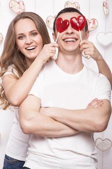 Jeune, belle femme et homme amoureux le jour de la saint-valentin avec des bonbons