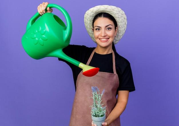 Jeune belle femme jardinier en tablier et chapeau tenant arrosoir et plante en pot à l'avant souriant debout sur le mur bleu