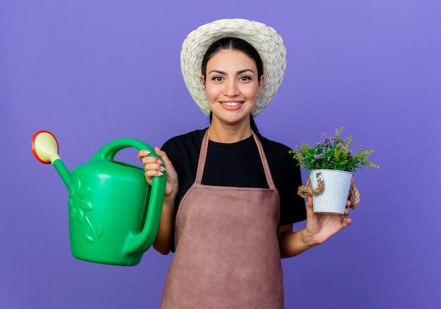 Jeune belle femme jardinier en tablier et chapeau tenant arrosoir et plante en pot à l'avant souriant joyeusement debout sur le mur bleu