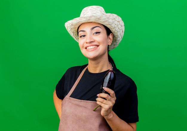 Jeune belle femme jardinier en tablier et chapeau tenant l'aubergine à l'avant souriant avec un visage heureux debout sur un mur vert