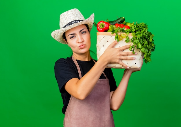 Jeune belle femme jardinier en tablier et chapeau tenant caisse pleine de légumes avec visage sérieux