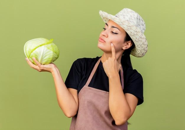 Jeune belle femme jardinier en tablier et chapeau tenant le chou en le regardant avec une expression pensive pensant debout sur un mur vert clair