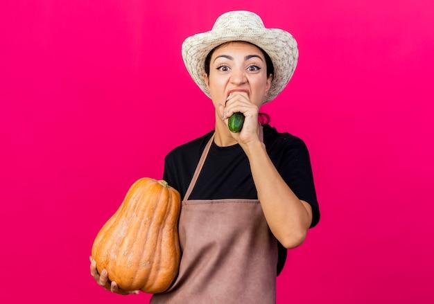 Jeune belle femme jardinier en tablier et chapeau tenant la citrouille et le concombre mordant debout sur le mur rose