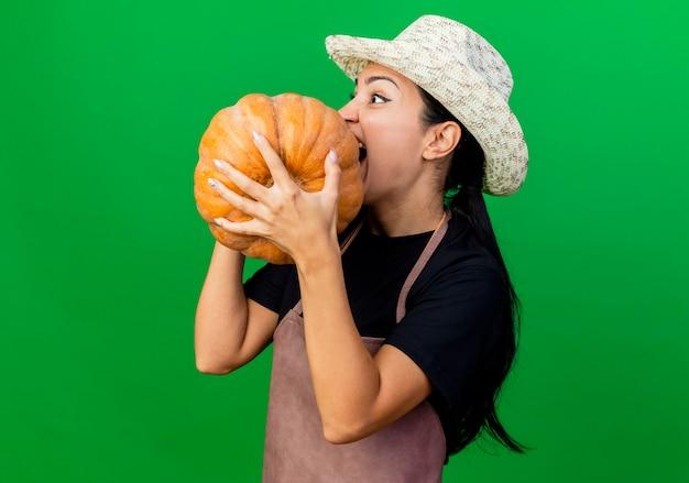 Jeune belle femme jardinier en tablier et chapeau tenant la citrouille en le mordant debout sur le mur vert