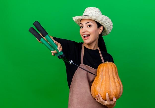Jeune belle femme jardinier en tablier et chapeau tenant la citrouille et tondeuse à haies regardant à l'avant souriant avec un visage heureux debout sur un mur vert