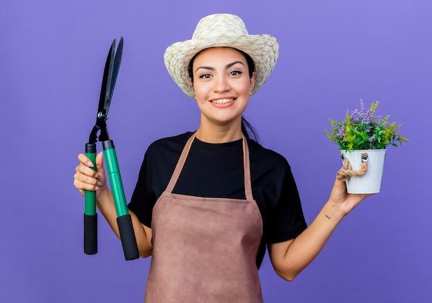 Jeune belle femme jardinier en tablier et chapeau tenant un coupe-haie et plante en pot souriant debout sur un mur bleu