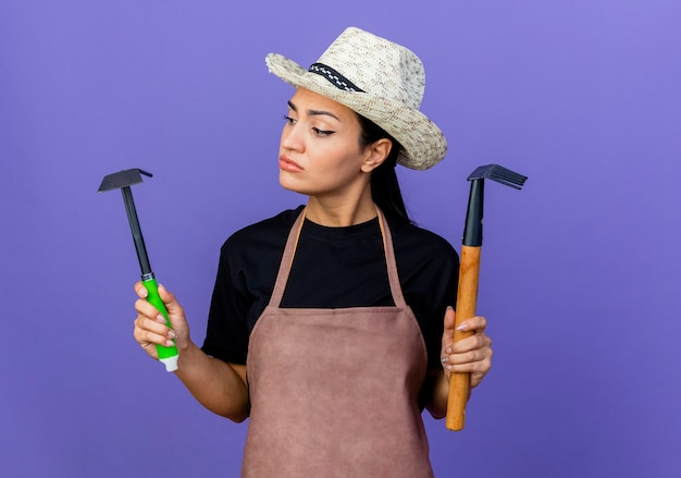 Jeune belle femme jardinier en tablier et chapeau tenant du matériel de jardinage à la confusion en essayant de faire un choix debout sur un mur bleu