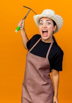 Jeune belle femme jardinier en tablier et chapeau tenant mattock à l'avant en criant d'être en colère debout sur un mur orange