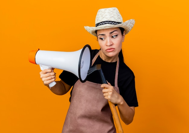 Jeune belle femme jardinier en tablier et chapeau tenant mini râteau et mégaphone à confus debout sur mur orange