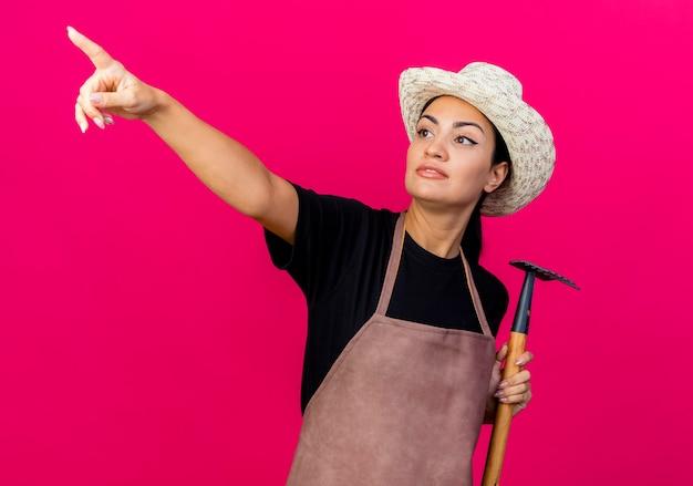Jeune belle femme jardinier en tablier et chapeau tenant mini râteau pointant sur quelque chose avec l'index debout sur le mur rose