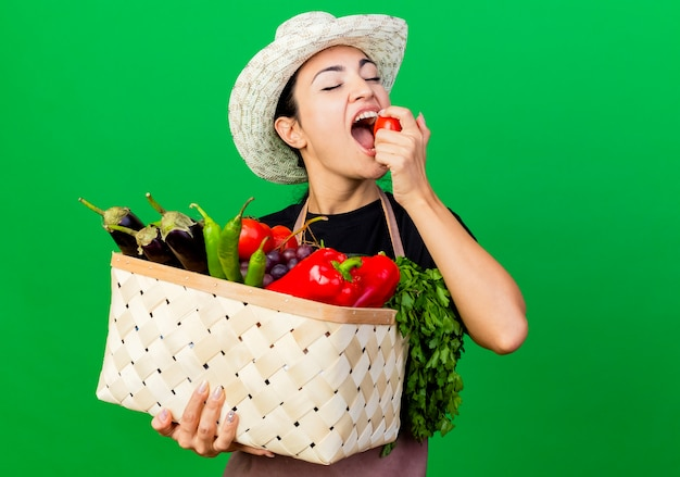 Jeune belle femme jardinier en tablier et chapeau tenant un panier plein de légumes mordant la tomate debout sur le mur vert
