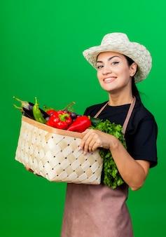 Jeune belle femme jardinier en tablier et chapeau tenant un panier plein de légumes souriant avec un visage heureux