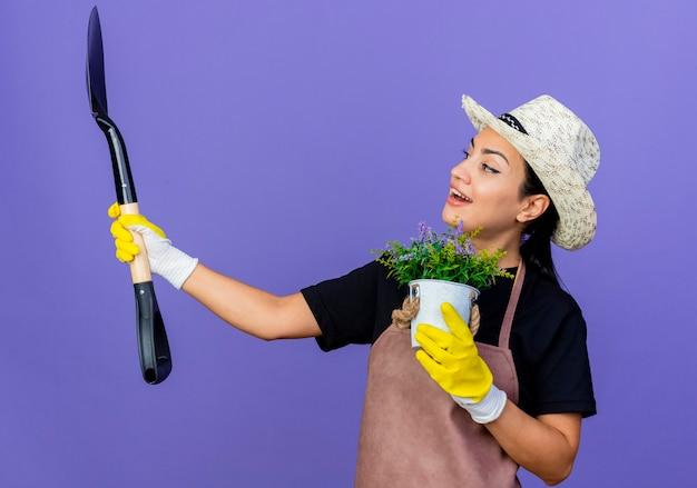 Jeune belle femme jardinier en tablier et chapeau tenant une pelle et une plante en pot heureux et positif souriant debout sur le mur bleu
