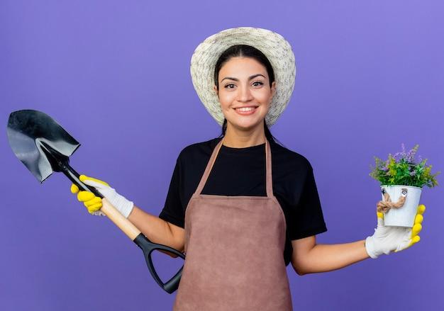 Jeune belle femme jardinier en tablier et chapeau tenant une pelle et une plante en pot souriant joyeusement debout sur un mur bleu