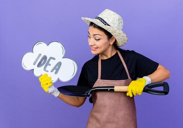 Jeune belle femme jardinier en tablier et chapeau tenant une pelle et un signe de bulle de parole avec idée de mot souriant debout sur un mur bleu