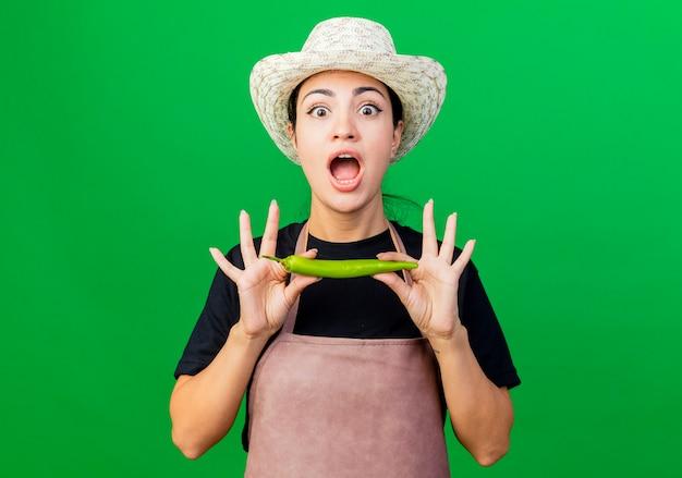 Jeune belle femme jardinier en tablier et chapeau tenant le piment vert étant surpris et étonné