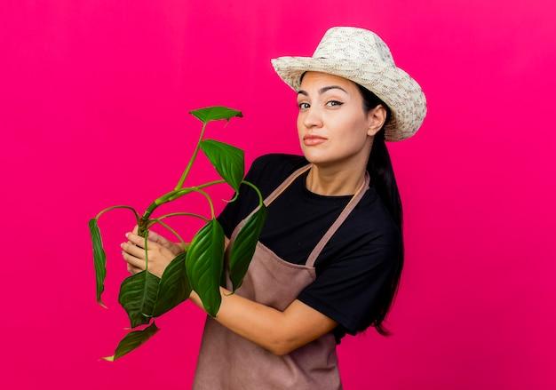 Jeune belle femme jardinier en tablier et chapeau tenant une plante à l'avant avec une expression sceptique debout sur un mur rose