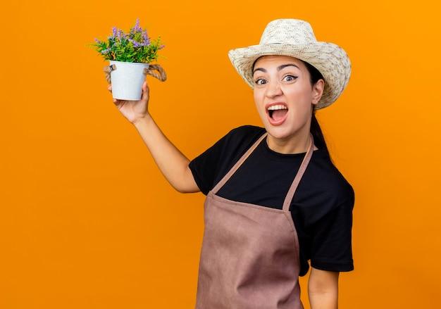 Jeune belle femme jardinier en tablier et chapeau tenant une plante en pot à l'avant d'être confus et mécontent debout sur un mur orange