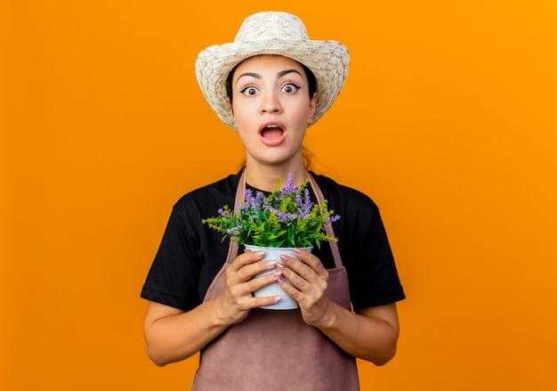 Jeune belle femme jardinier en tablier et chapeau tenant une plante en pot à l'avant d'être surpris debout sur un mur orange